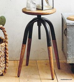 A cool, industrial-look stool with a distressed wood seat and legs on a curvy iron swivel base doubles as comfortable seating or an adjustable height display stand.