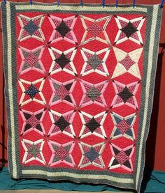 Pine Burr, 69x77, 1880-1910. Quite a graphic quilt that looks different depending on your point of view. As with most Pine Burrs I have met, this is quite heavy. The bright red plays against burgunday and pink, all enclosed in a triple border of green and cream prints. Hand pieced. The quilting is 5-6 st/in in contours and parallel lines.