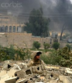 A U.S. Marine of the 1st. Marine Division conducts a search operation while columns of smoke rise after engagements in the in the war-torn city of Falluja, November 16, 2004. The U.S. military has begun an investigation into possible war crimes after a television pool report by NBC showed a Marine shooting dead a wounded and unarmed Iraqi in a Falluja mosque, officials said.