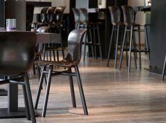 De zwarte Wendela als restaurant- of barstoeltjes. Op de foto aan stoere balkentafeltjes in het Hilton hotel in Den Haag.