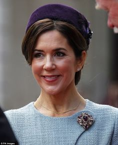 She topped off the statement look with a large diamond brooch, diamond earrings and a royal purple pillbox hat