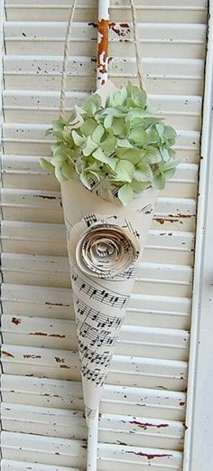 Paper cones made of sheet music hold decorative greenery.