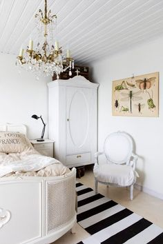 Bedroom with a sleigh bed, beautiful chandelier, and a tall wardrobe. Love the insect print on the wall and the suitcases stacked on the wardrobe. #chandelier #wardrobe #white