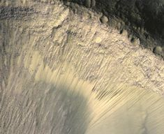 The steep slope of a crater, shown here, is located on the floor of Valles Marineris — a colossal canyon 2,500 miles long. The canyon is clearly visible from space, stretching across the Martian equator.