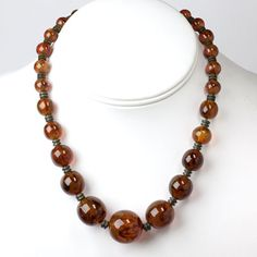 The cognac-colored graduated glass beads with black swirls that form this 1920s-1930s French Art Deco necklace are simply divine!