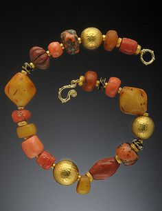 Hughes Bosca Designs | Necklace featuring antique African 'amber' and coral beads, combined with 18K Hand Forged Gold Clasp and space beads. {Price not published, please contact seller}