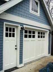 swing out garage doorsThese garage doors swing out Real Carriage Doors on a blue