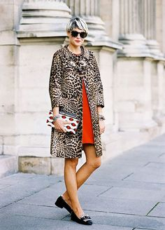 Leopard car coat worn over a red dress with black loafers