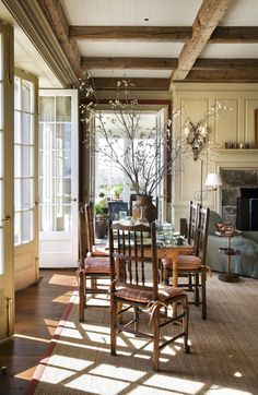 multiple french doors to blur the line between indoors & out, and rough beams in the ceiling
