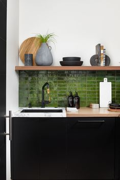 Sleek black cabinetry mix elegantly with these green cle tile backsplash. Exposed wood shelving and gorgeous Brizo tapware. A modern vignette worth falling for. #pantry #backkitchen #butlerpantry #modernhome