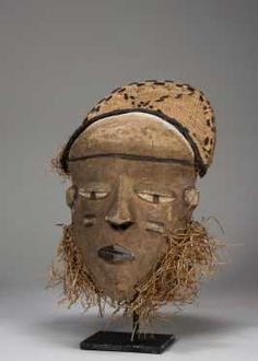 "A Pende mask. DR Congo; H: 9 1/2"" The mask carved simply with characteristic features, the eyes downcast, the nose wedge shaped and the lips closed and darkened. Remains of coif and fiber ruff. On a custom base."