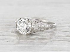 Antique Edwardian engagement ring made in platinum and centered with a GIA certified 1.79 carat old European cut diamond with I color and VS2 clarity. Accented with old European and single cut diamonds. Circa 1915.
