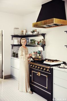 Dianna Agron in her stylish kitchen featurin ga La Cornue stove, marble countertops and chic white tiled flooring