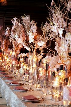 tall centerpieces with branches, candles, silver goblets