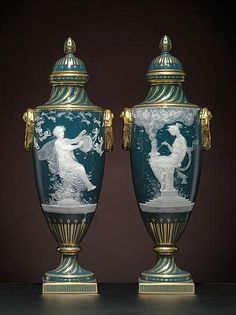 A PAIR OF MINTONS PEACOCK-BLUE PATE-SUR-PATE VASES AND COVERS <br />Circa 1900-1910, gilt crowned globe marks, impressed shape no. 2449 and various cyphers, gilder's K and interlaced C monogram, based on designs by L. Solon, both signed A(lboin) Birks<br />Of shield shape with spiral-fluted neck and socle, the shoulder flanked by pendant gilt wreath and lug handles, each painted and hand-tooled in white slip with a nymph seated on a columnar plinth either playing a tambourine or tending a…