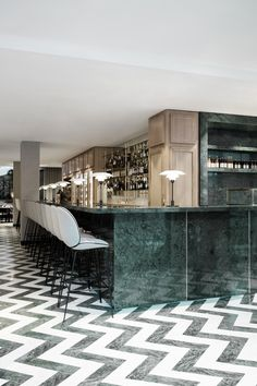 The expansive green marble bar hosts GUBI's Beetle Bar Stools. The entire space is filled with a pleasant green-focused color palette that's offset by shades of gray and brass details.
