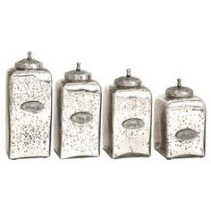 """Perfect for holding office supplies in the den or cotton balls in your powder room, this mercury glass jar set features tailed finial lids and numbered metal emblems cast with vintage-style writing.   Product: Small lidded jarMedium lidded jarLarge lidded jarExtra large lidded jar   Construction Material: Mercury glass and iron  Color: Silver  Features:Made in India  Dimensions: Small: 9.5"""" H x 4.75"""" W x 4.75"""" D Medium: 10.5"""" H x 4.75"""" W x 4.75"""" DLarge:  11.5"""" H x 4.75"""" W x ..."""