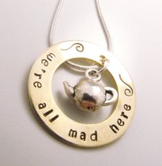 "^INSPIRATION...This brass washer is hand stamped with the phrase ""we're all mad here"" from Alice In Wonderland. If you are looking for something a little different to match your quirky side, I do belive this is the hand stamped pendant for you. To make this pendant perfect, I added the cutest teapot charm that fits just inside the washer as a reminder of the Mad Tea Party scene. This pendant comes on an 18"" sterling silver snake chain."