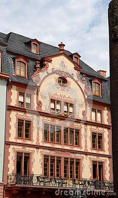 Photo taken with an elegant and sober palace of Mainz in Germany. In the picture you see at the bottom, a large balcony with several chairs with two large French windows and a large window to six modules. The upper windows are similar. Those of the third floor, in the attic, however, are smaller and with partially drawn curtains.