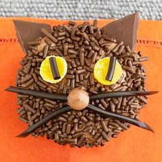 Chocolate sprinkles, gumdrops, and licorice combine for a fuzzy cat face destined to make birthday kids smile. 1. Frost cupcakes with chocolate frosting; coat generously with chocolate sprinkles. 2. To make eyes, cut a 1/8-inch-thick slice off the larger end of two yellow gumdrops; add a small piece of shoestring licorice to the cut side of each slice. Insert into frosted cupcake. 3. For ears, cut chocolate coating dots into triangle shapes with a paring knife. Insert ears into frosting on…