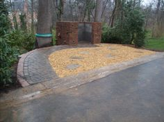 Gravel parking area with walkway. Storage area built with brick and natural stone