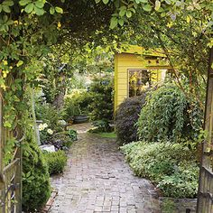 Love the bower, the brick path and the little yellow shed.