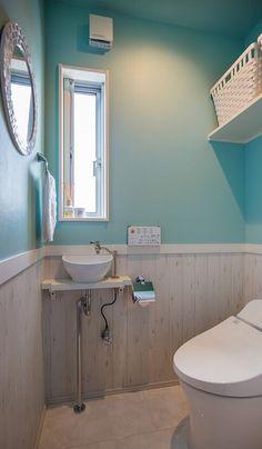 テーマはカリフォルニア風。ライトブルーのクロスに木目調のホワイトの腰壁が、トイレを爽やかな印象に。