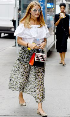 Olivia Palermo pairs an off-the-shoulder white shirt with a flowy floral skirt, flats, white sunglasses, and a black and red handbag