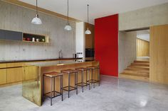 concrete floored kitchen with pendant lights and brass clad island.