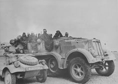 German half-track tractor Sd.Kfz.7 with 88-mm anti-aircraft gun on the trailer of the Afrika Korps near the passenger army vehicles KubelwagenVW Typ 82.
