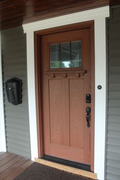 Front Door Craftsman Style with white trim windswept smoke siding & Cherry entry door accented by craftsman hardware. Integrated hidden ...