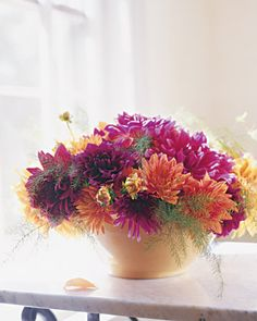 Late-Summer Dahlias  A yellowware kitchen bowl of late-summer dahlias would certainly be lovely enough on its own, but adding a contrasting element -- here, wispy asparagus fronds -- make the hot colors and spiky forms even more striking.