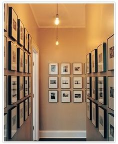 Use of the same exact frames containing different sized photographs, placed in a very organized, streamlined manner on the wall