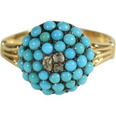 A beautiful ring from about 1860 of pave set turquoise with 3 rose cut diamonds in the center. The stones are set in 12kt gold. The round disc