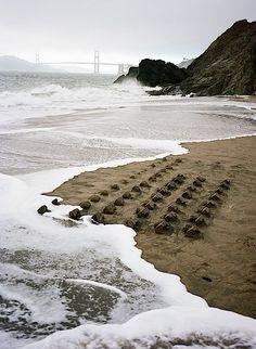 Ein ganzer Sandburgen-Vorort verschwindet im Meer
