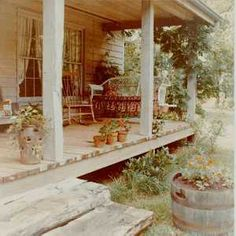 Country Front Porch    Wood porch floors made of pressure treated lumber are excellent for a country house since they are easy to maintain. No mud stains from friendly pets will remain as in the case of a concrete porch floor. Rough 6x6 inch posts are used with steps sawn from a large log. An old wicker couch is made into a porch swing.