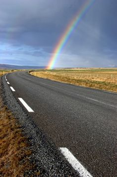 curving road leads to the start of the rainbow