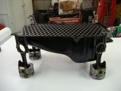 Oil pan grill with piston legs. The grill even has a grate in the sump so the charcoal can get airflow, the top is hinged.