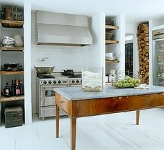 Rustic Refinement Add a marble slab to a solid wood table to create a DIY custom kitchen island. The shiny metal stove and hood looks modern and sleek, and the reclaimed wood open shelves add a touch of rustic design to the refined neutral space.