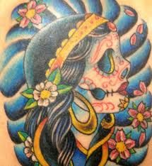 I want a day of the dead skull on my side with violets (to represent my fiance) and marigolds (to represent me).  Later I can add my children's birth month flowers.