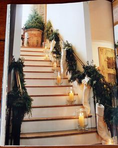 This stairwell looks so inviting with the simple hurricane lamps, cream colored stockings, garland and the fir tree potted at the top of the stairs.