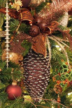 A blown-glass pinecone decoration with a rust-colored, wired woodgrain print ribbon and rustic bells and feathers. Very nice.