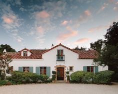 Inspired by Andalusian architecture,  Montecito's Emmor J. Miley House, crafted by Mary McLaughlin Craig, features white plaster walls with a sandstone-framed entryway and a black iron balcony, traditional to Spain.