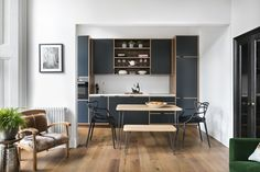 """""""The bespoke kitchen made of [plywood and walnut] is a complete work of art; the brief was to create a practical functioning kitchen but one that didn't look like your average kitchen — it needed to have the appearance of a piece of furniture so it would sit more comfortably in its surrounds."""""""
