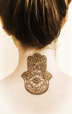hamsa tattoo | hamsa hand on neck back black grey tattoo female neck turned down with the endless knot in place of the eye