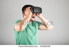 Handsome man wearing virtual reality glasses isolated on a gray background