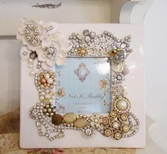 "Recycled jewelry decorated frame the white frame makes this very ""girly""."