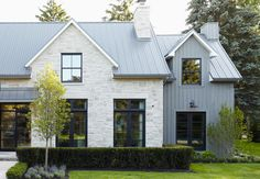 Metal roof, stone, vertical siding, black windows, and color scheme