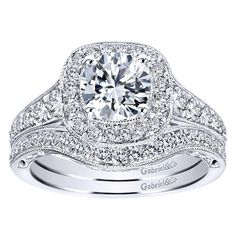 14k white gold 1.60cttw cushion shaped halo diamond engagement ring with 1ct round diamond. Bead set G/SI diamonds taper down the shank of this intricate vintag