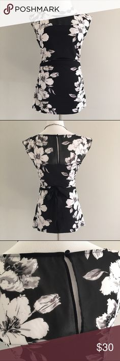 WHBM sleeveless black top with white floral print White House Black Market stretchy sleeveless floral print top has a translucent black tie at waist. Size medium, worn once or twice. Translucent upper portion and tie belt are 100% polyester and the stretchy lower portion is 95% polyester and 5% spandex. Machine washable. White House Black Market Tops Tank Tops